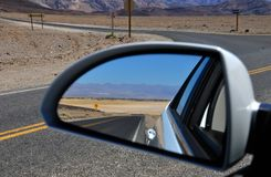 Desert road in rear-view mirror. Desert road in Death Valley National Park as reflected by a rear-view mirror Royalty Free Stock Photography