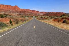 Desert road through red cliffs Stock Photos