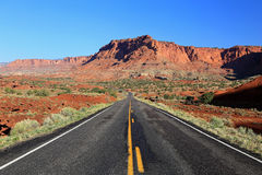 Desert road through red cliffs Stock Photo