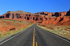 Desert road through red cliffs Stock Images