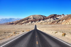Desert road towards mountain range at Death Valley. Desert road towards mountain range at Death Valley, travel concept, focus on mountains, USA Royalty Free Stock Images