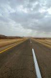 Desert road. Under dramatic cloudy sky. Arabah, Israel Royalty Free Stock Images