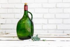 Vintage green glass bottle and desert rose Stock Photography