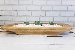 Desert rose on white pebbles inside a wooden bowl Royalty Free Stock Photos