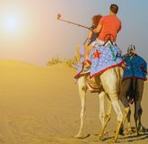 Desert safari sunrise selfie stick shot smartphone. Tourist attractions sand desert sunrise safari camels using a selfie stick shot mobile phone, Tourists are stock photography