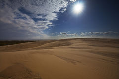Desert sand dunes, clouds and bright sun Royalty Free Stock Images