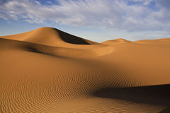 Desert sand dunes with cloudy blue sky Royalty Free Stock Image