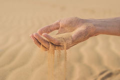 Desert, sand puffs through the fingers of a man`s hand.  stock photography