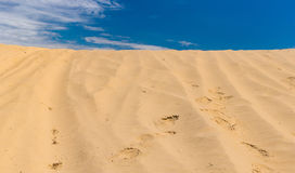 Desert sands against blue sky Stock Photography