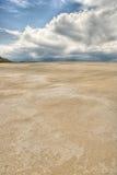 Desert sands under distant clouds Stock Photos