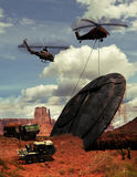 Desert secrets. Helicopter pulling out of the ground, a flying saucer in the desert, under the supervision of several people and another helicopter Stock Image