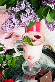Desert smoothies with strawberries. Smoothies with strawberries on a tin tray with chunks of chocolate and a sprig of mint in the foreground and a red vase with Royalty Free Stock Photos