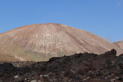 Desert stone volcanic landscape in Lanzarote, Canary Islands. Timanfaya National Park, Canary Islands, Spain. The cone of volcano on background of blue sky Stock Photography