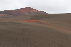 Desert stone volcanic landscape in Lanzarote, Canary Islands. Timanfaya National Park, Canary Islands, Spain. The cone of volcano on background of blue sky Stock Image