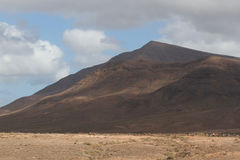 Desert stone volcanic landscape in Lanzarote, Canary Islands. Timanfaya National Park, Canary Islands, Spain. The cone of volcano on background of blue sky Royalty Free Stock Images