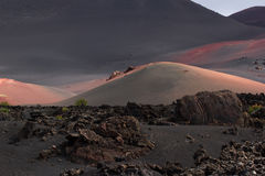 Desert stone volcanic landscape in Lanzarote, Canary Islands. Timanfaya National Park, Canary Islands, Spain. The cone of volcano on background of blue sky Royalty Free Stock Image