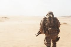 Desert storm. Portrait of United states airborne infantryman moving through desert storm. Cropped portrait, overcome difficulties concept Stock Photo