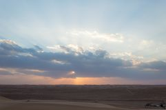 Desert sunset. Sunset in a desert with sun covered behind a cloud Stock Photo