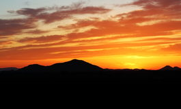 Desert Sunset. With bright colors and mountains in background Royalty Free Stock Photography