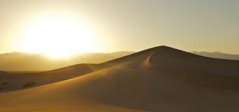 Desert Sunset. The bright sun flares the lens as it sets behind a desert sand dune Stock Photo