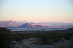 Desert at sunset. A pink sunset over the mountains in the desert causing a mirage to appear Stock Image