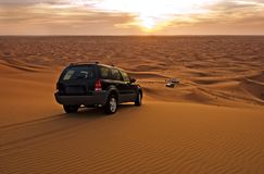 Desert SUV 01. Desert scene at twilight with SUV overlooking other suvs royalty free stock photography