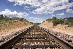 Desert Train tracks. Train tracks run through a hill in the desert, under a partly cloudy sky Royalty Free Stock Photos