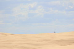 Into the desert. Two man are walking in the sand dunes landscape of Anna Bay - the largest sand dune system in Australia Royalty Free Stock Images