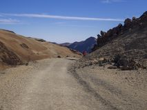 Desert volcanic landscape with couple of hikers in red clothes w. Alking on road to volcano pico del teide with orange and purple mountain with clear blue sky Royalty Free Stock Photos