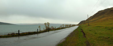 Desert wet road along the lake. Khakassia Royalty Free Stock Image