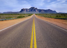 Desert wilderness road leading to mountain. Royalty Free Stock Images