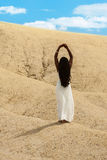 Desert woman reaching for the sky. A beautiful, barefooted woman reaches for the sky Royalty Free Stock Photography