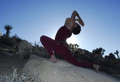 Desert Yoga Diva. Semi silhouette of Woman in yoga lunge and backbend pose outdoors in the desert Stock Photo