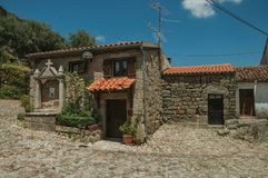 Deserted alley and old small house with stone walls. Deserted alley and charming old small house with stone niche for saints, in a sunny day at Belmonte. A cute stock photography