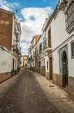 Deserted alley with old terraced buildings and worn plaster in Caceres. Caceres, Spain - July 02, 2018. Deserted alley with old terraced buildings and worn royalty free stock photo