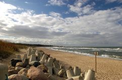 Deserted beach. A deserted, windswept beach with concrete objects in the foreground Royalty Free Stock Image