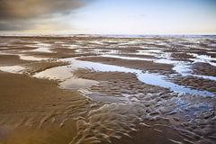 Deserted Beach At Low Tide Stock Photos