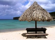 Deserted beach on Curacao before a thunderstorm. Lonely umbrella on the beautiful beach of the island of Curacao stock image