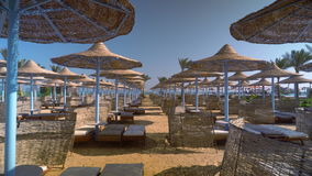 A deserted beach in the early morning, beach umbrellas and sun loungers are empty. stock footage