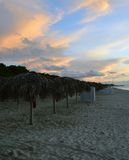 Deserted beach in evening light. Deserted beach with palm tree parasols at Varadero, Cuba (no people stock image