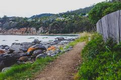 Deserted beach in Hobart, Tasmania with rocks and walkpath  in t. Deserted beach in Hobart, Tasmania with rocks and walkpath in the foreground on an overcast day Stock Photos