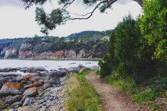 Deserted beach in Hobart, Tasmania with rocks and walkpath  in t. Deserted beach in Hobart, Tasmania with rocks and walkpath in the foreground on an overcast day Royalty Free Stock Photo