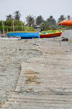 Deserted beach with old wooden pier and colourful fishing boats Royalty Free Stock Image
