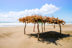 Deserted beach and sun canopy. Deserted wild sea beach and sun canopy of branches. Summer vacation on the island Stock Image