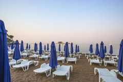 A deserted beach with sun loungers and umbrellas in the early morning. On the beach sand. The morning of 2017 is Europe Royalty Free Stock Image