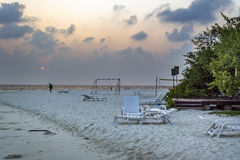 A deserted beach with sunbeds at sunset royalty free stock photo