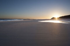 Deserted Beach at Sunrise. A deserted beach with the sun just rising over the sand dunes Royalty Free Stock Photo