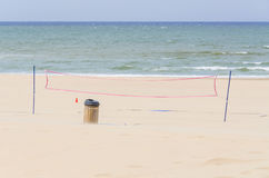 Deserted beach, volleyball net and dustbin Royalty Free Stock Image