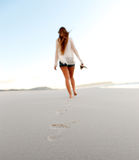Deserted beach walking. Woman walks alone on a deserted beach, solitude, serene, lonely concept. carefree vacation in nature Royalty Free Stock Images