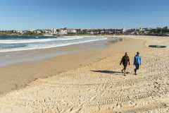 Bondi Beach Deserted. A virtually deserted Bondi Beach after the huge winter storm on the night of 6th June 2012. two walkers rugged up against the cold wind Stock Photos